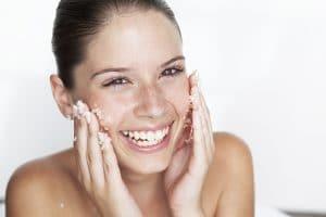Woman scrubbing sugar on her face --- Image by © GretaMarie/cultura/Corbis